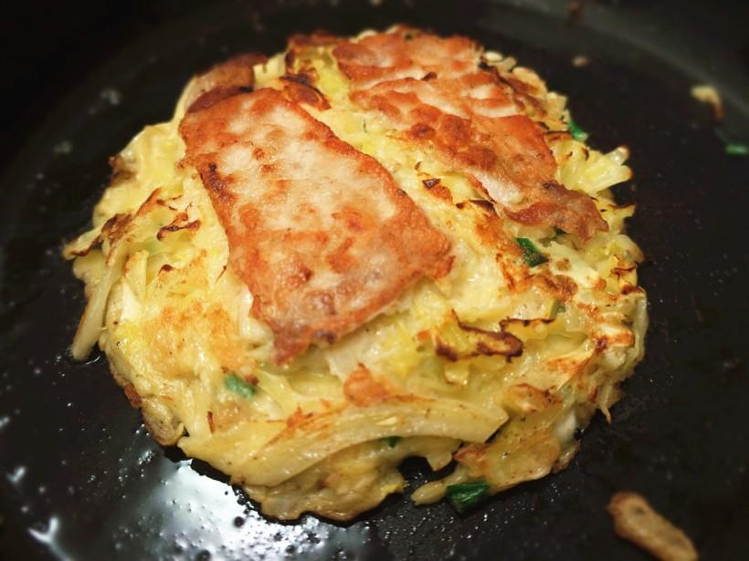 反轉後(然後豬肉片向下)慢火煎個5份鐘,但這次要把鍋蓋上煮,這樣中心的捲心菜才能全熟。打開再反回來查看豬肉是否已熟和好好地貼著燒餅(如圖)。